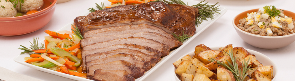 sliced brisket with vegetables on white platter surrounded by side dishes