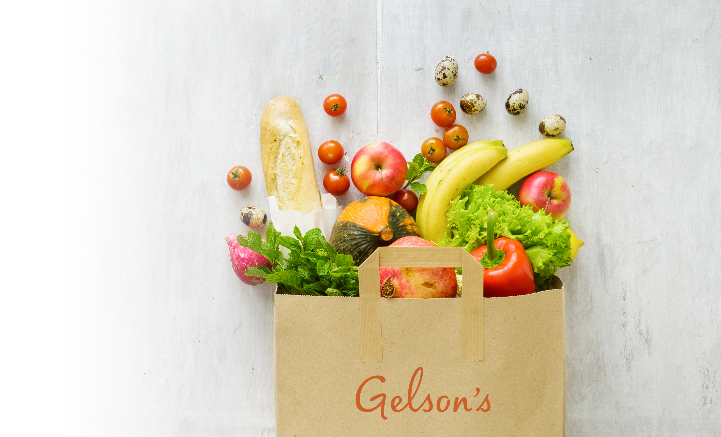 Grocery bag with Gelson's logo filled with fresh fruit and vegetables