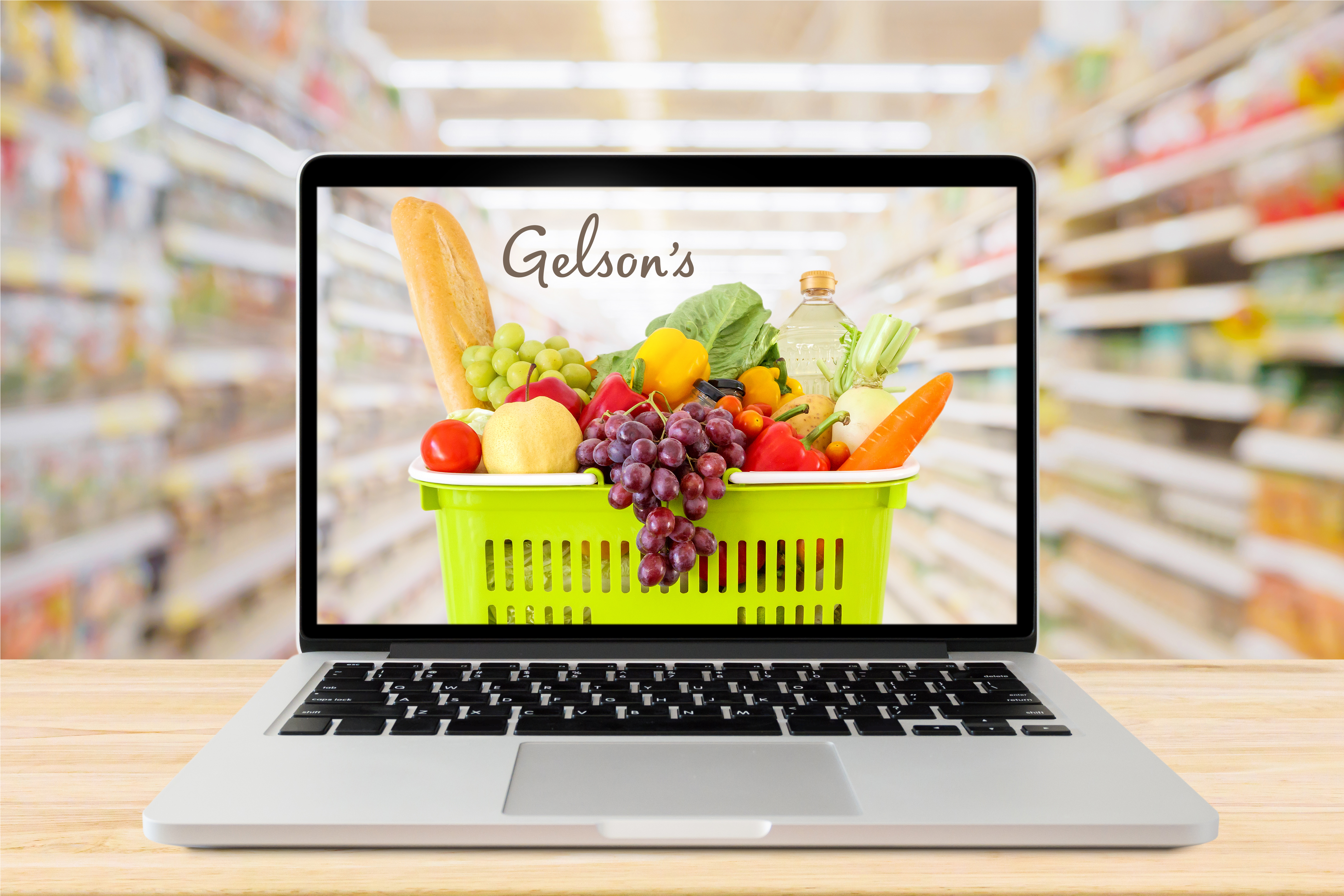 laptop with photo of cart with groceries and Gelson's logo background is blurred grocery store aisle